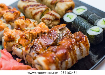 Assortment of delicious fresh, tempura and baked sushi maki with salmon, eel, cucumber, avocado, scrambled eggs, shrimp and unagi sauce - stock photo