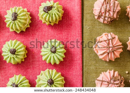 Assortment of delicious green and pink cookies on colorful napkins - stock photo
