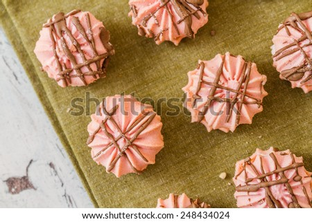 Assortment of delicious pink cookies with colorful napkins on white wooden background - stock photo