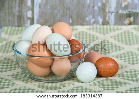 Assortment of different color, fresh, chicken eggs in a glass bowl. Green shade kitchen textile background.