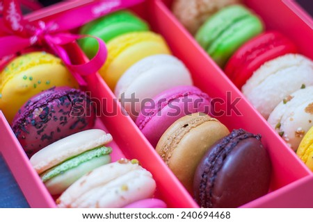 Assortment of different colored macaroons in pink box with a ribbon and bow - stock photo