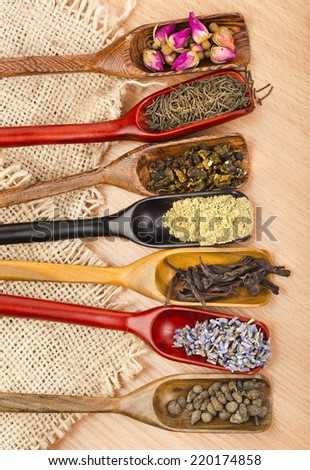 assortment of different dry tea in scoops on wooden table background, top view - stock photo