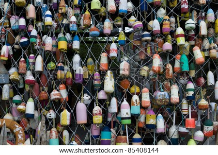 Assortment of different fishing buoys hanging from a net - stock photo