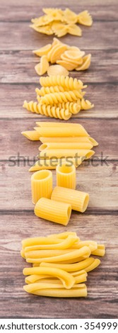 Assortment of different shape pastas over wooden background - stock photo