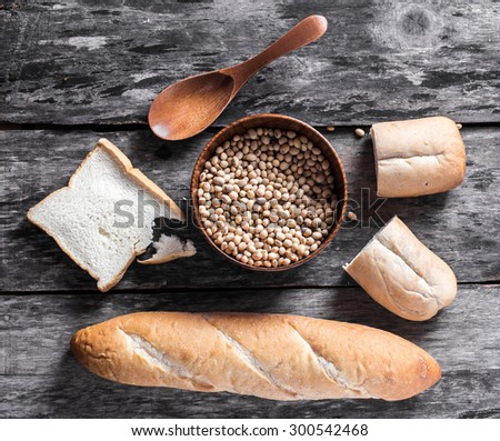 Assortment of different types of bread on wood background - stock photo