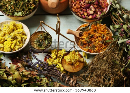 Assortment of dry medicinal herbs in bowls on wooden background top view - stock photo