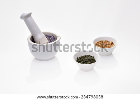 Assortment of dry medicinal herbs in porcelain bowl and mortar with pestle (clitoria, melissa and sapindus) - stock photo