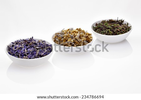 Assortment of dry medicinal herbs in porcelain bowls (immortelle, melissa, clitoria)