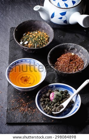 Assortment of dry tea, cup of hot tea and teapot. Green tea, black tea, green tea with rice, rooibos, dry rose buds in porcelan and old metal chinese bowls. Black textured slate background. - stock photo