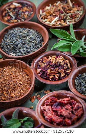 Assortment of dry tea in bowls - stock photo