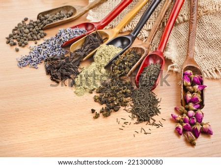 assortment of dry tea in scoops on wooden surface background, top view - stock photo