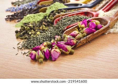 assortment of dry tea in scoops on wooden table background - stock photo