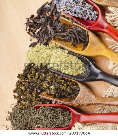 assortment of dry tea in scoops top view close up on wooden background - stock photo
