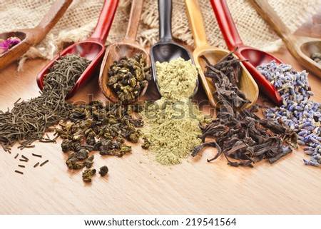 assortment of dry tea in spoon scoops close up  on wooden table background - stock photo