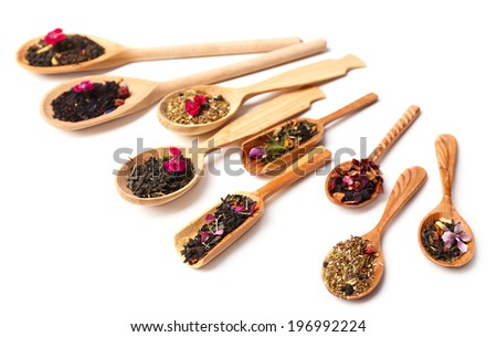 Assortment of dry tea in wooden spoons,  isolated on white - stock photo