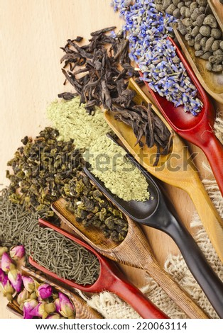 assortment of dry tea leaves and addition in spoon scoops close up  on wooden table background - stock photo