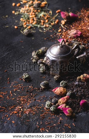 Assortment of dry tea with tea strainer as small teapot. Green tea, black tae, green tea with rice, rooibos, dry rose buds. Black textured slate background. With copy space on left. - stock photo