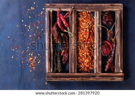 Assortment of dryed whole and flakes red hot chili peppers in wooden box over dark blue canvas as background - stock photo