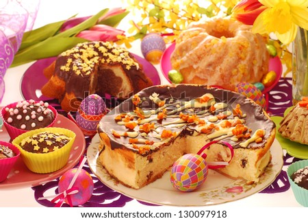 assortment of easter confectionery ( cheese cake, ring cakes,muffins ) on colorful festive table - stock photo