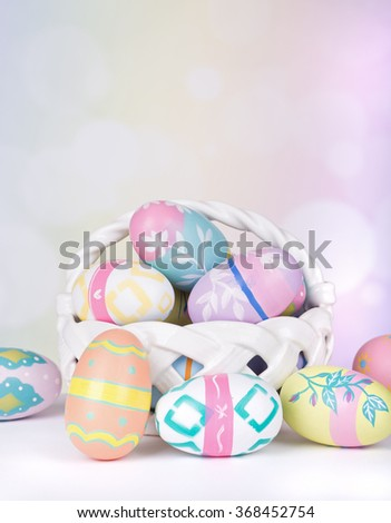 Assortment of Easter eggs and basket on a colorful background