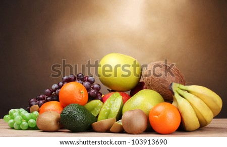 Assortment of exotic fruits on wooden table on brown background - stock photo