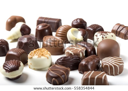 Assortment of fine chocolate candies, white, dark, and milk chocolate over white background