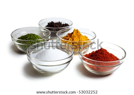 Assortment of five spices ( pepper, herbs, salt, curry, chili ) on white background