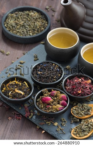 assortment of fragrant dried teas and green tea, top view, vertical, close-up - stock photo