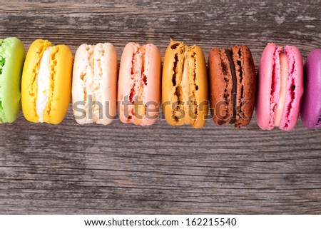 Assortment of French macaroons in rainbow colours, over old wood background with space for your text. - stock photo