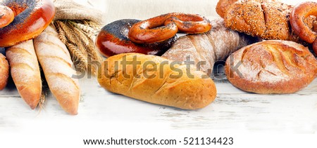 Assortment of  fresh baked bread on a wooden table isolated on a white background