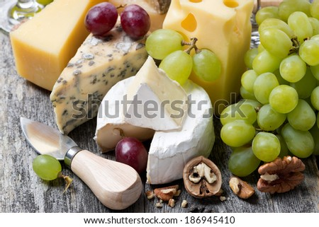 assortment of fresh cheeses, grapes and walnuts on a wooden background, close-up - stock photo