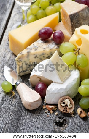 assortment of fresh cheeses, grapes and walnuts on a wooden background, close-up, vertical - stock photo