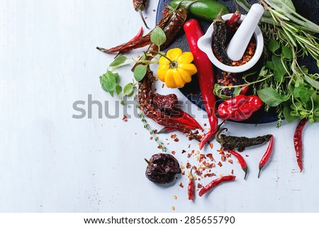 Assortment of fresh, dryed and flakes hot chili peppers and fresh herbs with white ceramic mortar on dark blue cutting board over light blue wooden background. Top view - stock photo