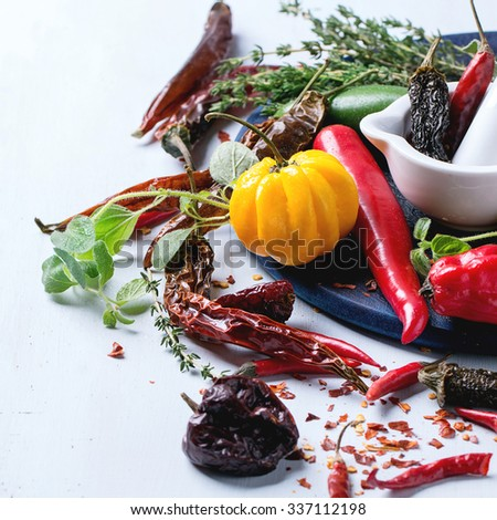 Assortment of fresh, dryed and flakes hot chili peppers and fresh herbs with white ceramic mortar on dark blue cutting board over light blue wooden background. Selective focus. Square image - stock photo