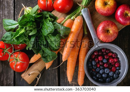 Assortment of fresh fruits, vegetables and berries. Bunch of carrots, spinach, tomatoes and red apples on chopping board, blueberries and cranberries in old colander over old wooden table. Top view - stock photo