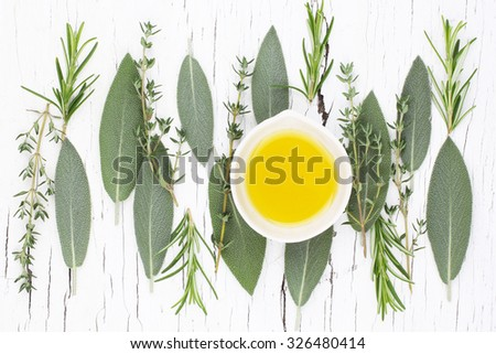 Assortment of fresh herbs thyme, rosemary, sage and oil over light white wooden background. Top view.  - stock photo