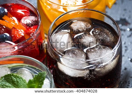 assortment of fresh iced fruit drinks on a dark background, top view, closeup, horizontal - stock photo