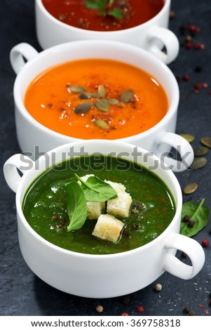assortment of fresh vegetable cream soup on a black background, vertical, closeup