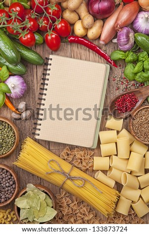 Assortment of fresh vegetables and blank recipe book on a wooden background - stock photo