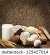 assortment of freshly baked bread and organic products on wooden table - stock photo