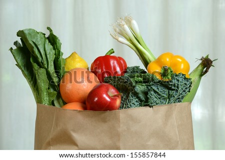 Assortment of fruits and vegetables in paper bag with curtain in background