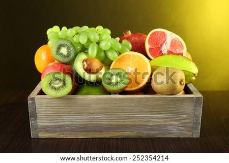 Assortment of fruits in box on dark yellow background - stock photo