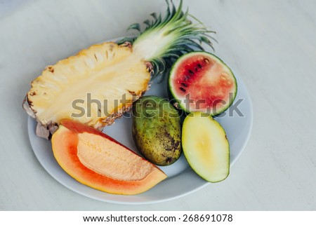Assortment of fruits on the plate on the table. Exotic fruits variety on white table. Sliced fresh fruits on table - stock photo