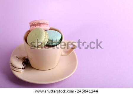 Assortment of gentle colorful macaroons in colorful mug on color background - stock photo