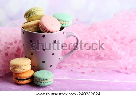 Assortment of gentle colorful macaroons in colorful mug on color wooden table, on light background - stock photo