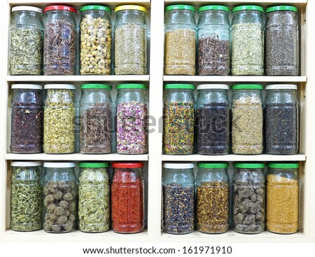 assortment of glass jars on shelves in herbalist shop in marrakesh, morocco, containing herbs and spices for medicinal and culinary purposes - stock photo