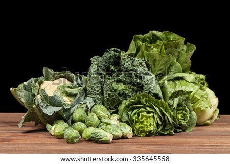 Assortment of green vegetables on wooden surface - stock photo