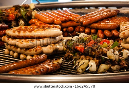 Assortment of grilled sausages and kebabs on big round grill at Christmas market in Paris. Selective focus on the sausages on left side. - stock photo