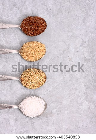 Assortment of groats and spices on old wooden table - stock photo