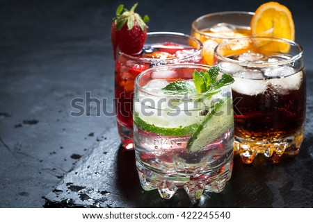assortment of iced fruit drinks on a dark background, horizontal - stock photo